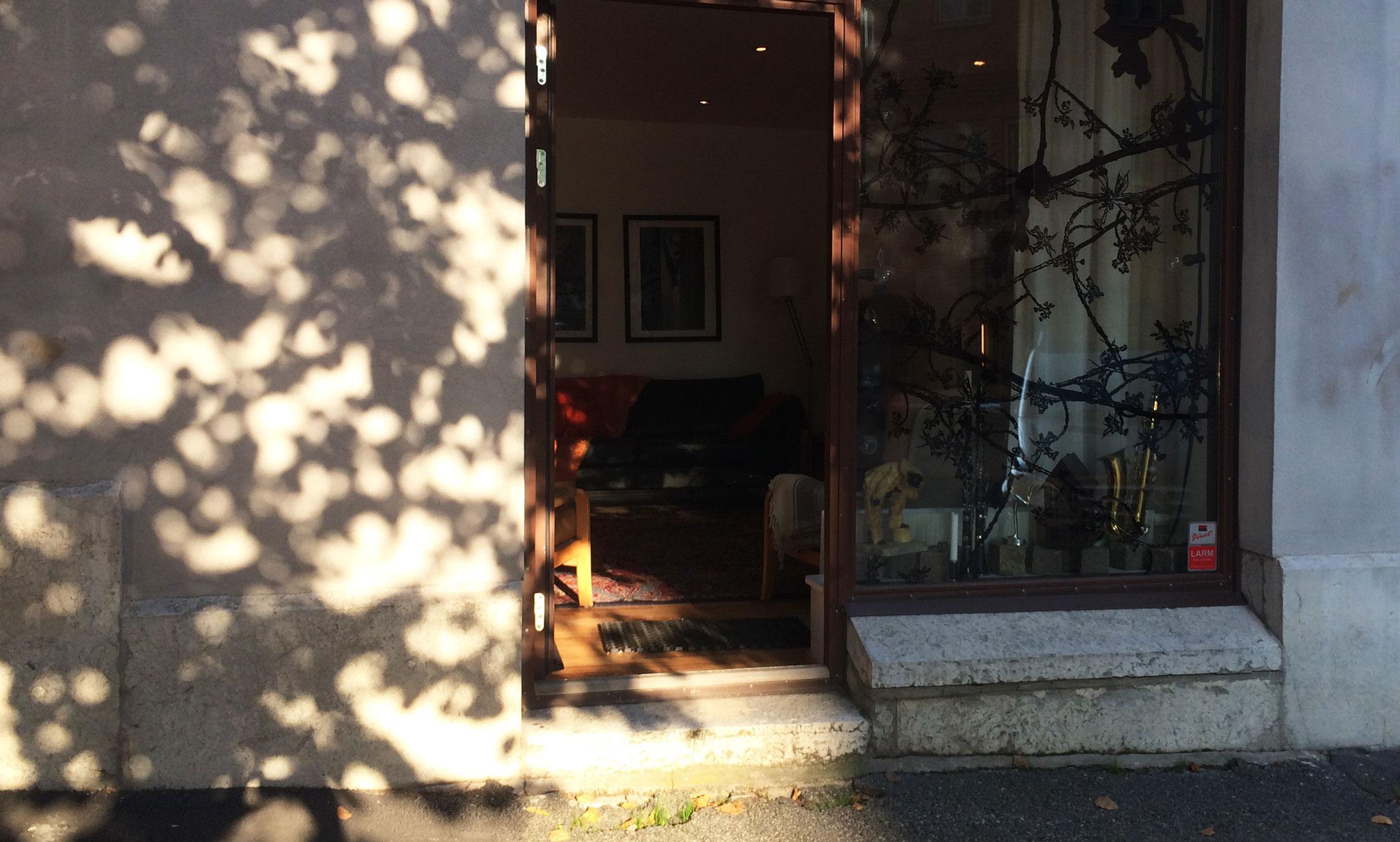 Bild på KASTELLGATAN 16 Entrén i eftermiddagssol med dörren öppen mot gatan – alldeles intill linden, strax mittemot surdegsbageriet Alvar & Ivar och med restaurangen Dubbel Dubbel runt hörnet. September 2014.